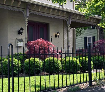 aluminum fencing and ornate Victorian roof brackets highlight this elegant front entrance to this home.